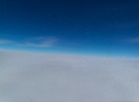 Snow above the clouds. A picture from the window of the plane.