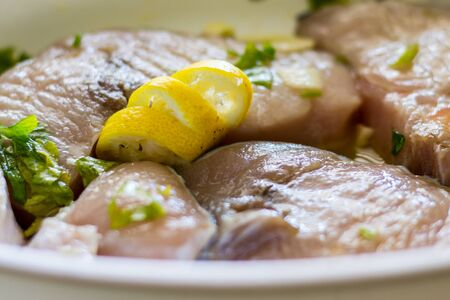 Marinated swordfish in a bowl with lemon, oil, garlic, parsley Imagens