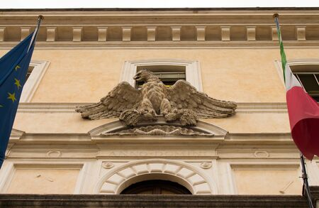 Facade of a building in Rome, view of the eagle next to the Italian and European flags