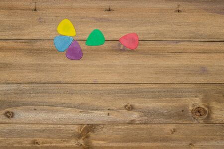 acoustic guitar accessories, colorful picks on wooden background