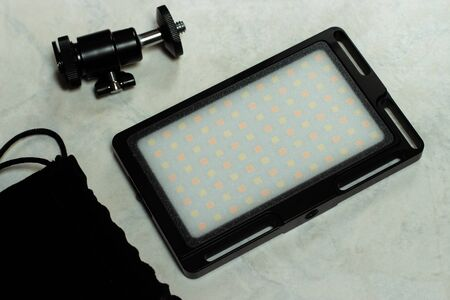 The image shows an off LED lamp with internal rechargeable battery ready to be mounted on a DSLR to take photos and videos, isolated on a white background. Photographic equipment, LED video light with its accessories.