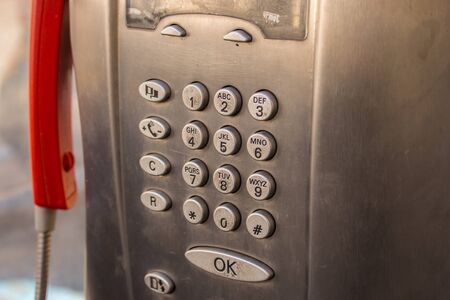 Numeric keypad of an old Italian telephone booth in the city