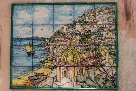 Typical Vietri sul mare ceramic tiles attached to the wall of a house along a narrow street in the city