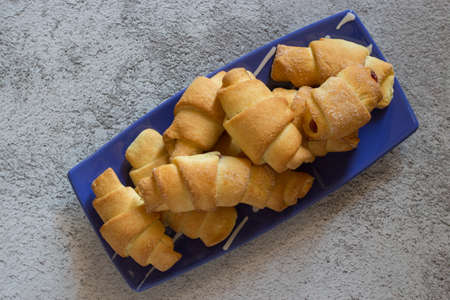 Crescent-shaped sweet shortcrust croissants filled with black cherry jam.