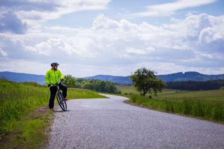 Man riding bike, making short break, enjoying beautiful nature. 스톡 콘텐츠