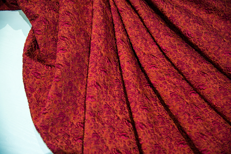 Red fabric for dresses, With flower patterns, fabric background, folds of fabric