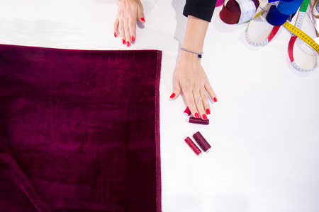 Womens hands and cloths, red cloth lies on the table, hand reaches for the threads