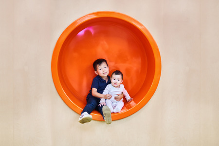 Children brother and sister, boy and girl are sitting in an orange circle on a wooden background