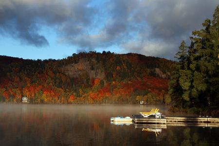 山湖の美しいカラフルな秋の朝。秋の紅葉とケベック州の反射と山と湖霧パノラマ。カナダの秋。