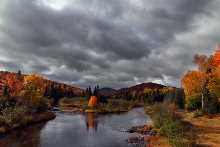 山川に美しい秋の朝。劇的な秋の空。昇る太陽の光線で黄色の木。秋の風景です。ケベック州。カナダの秋。