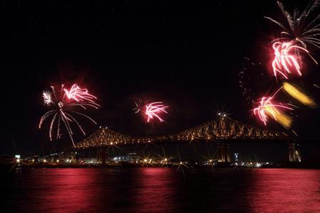 カラフルな花火は、橋、反射水で爆発します。モントリオールの 375th 周年記念。明るいカラフルなインタラクティブなジャック カルチェ橋。橋の夜