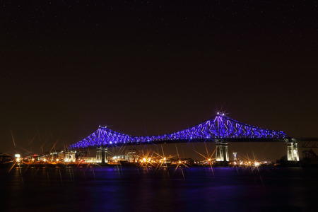 civic: Jacques Cartier Bridge Illumination in Montreal, reflection in water. Montreals 375th anniversary. Luminous colorful interactive Jacques Cartier Bridge. Bridge panoramic colorful silhouette by night.