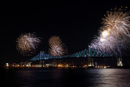 bridge over water: Colorful fireworks explode over a bridge, reflection in water. Montreals 375th anniversary. Luminous colorful interactive Jacques Cartier Bridge. Bridge panoramic colorful silhouette by night. Stock Photo