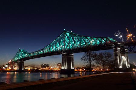 Jacques Cartier Bridge Illumination in Montreal, reflection in water. Montreals 375th anniversary. Luminous colorful interactive Jacques Cartier Bridge. Bridge panoramic colorful silhouette by night.