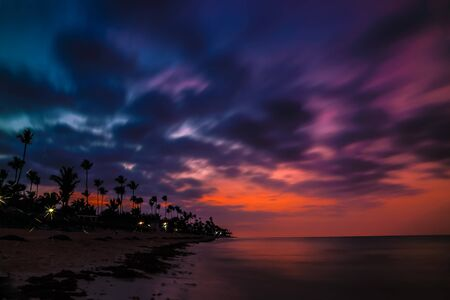 Dramatic sunset over the exotic beach, with palms. Incredible sunset on a tropical island in the ocean. Colorful dramatic sky with sunset.