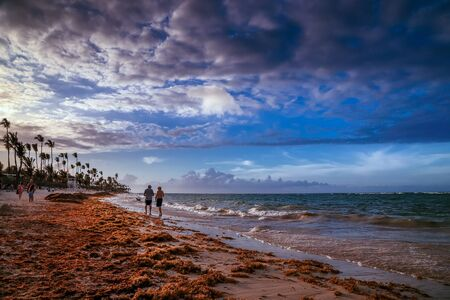 Sunset in Punta Cana in Dominican Republic. A Couple Walking at the Resort Tropical Beach in Punta Cana, Dominican Republic. Dramatic sunset over the exotic beach, Punta Cana, Dominican Republic, with palms and white sand beaches for a relaxing beach. Stock Photo