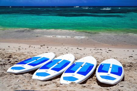 Surfboards on the beach. Surfing board on the beach with ocean view nobody. surfboards abandoned on an empty sandy beach with waves in distance. Summer sunny day on the shores of the Atlantic Ocean. Emerald water with white sand and blue sky. Bavaro beach.