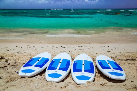 Surfboards on the beach. Surfing board on the beach with ocean view nobody. surfboards abandoned on an empty sandy beach with waves in distance. Amazing tropical beach with surfboards against azure ocean, white sand and blue sky. Caribbean wild nature scenery near the beach in Punta Cana. Stock fotó