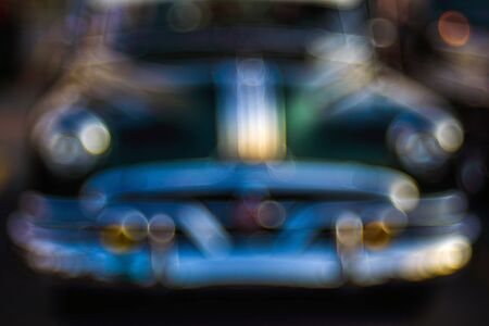 Abstract background with bokeh defocused classic car. Colorful abstract background retro car. Boke background with copy space. Close-up view vintage auto details with bubble bokeh effect.