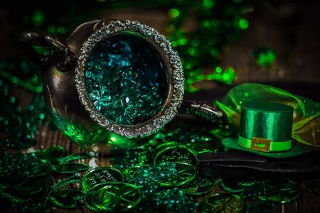 St.Patrick's day holiday symbol. Shamrocks, coins, leprechaun hat and antique silver pot on an old rustic wood background. Close up view. Selective focus. Bokeh.