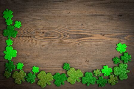St Patricks Day border of shamrocks on vintage style wood background. St.Patrick's day holiday symbol. Lucky charms. Top view, copy space.
