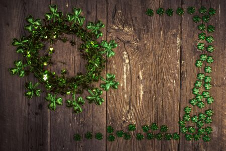 St. Patricks Day composition. Shamrock wreath, shamrocks on an old rustic wood background. St.Patrick's day holiday symbol. Top view, copy space.