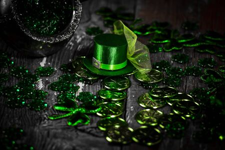 St. Patricks Day composition. Shamrocks, coins, leprechaun hat and silver pot on vintage style wood background. St.Patrick's day holiday symbol. Top view, copy space.