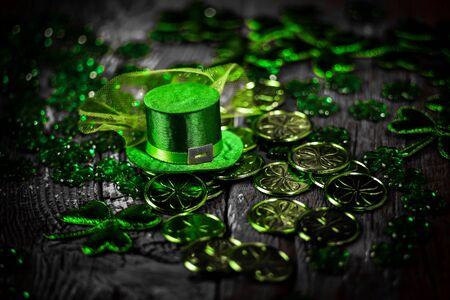 St. Patricks Day composition. Shamrocks, coins, leprechaun hat on vintage style wood background. St.Patrick's day holiday symbol. Close up view. Selective focus. Bokeh.