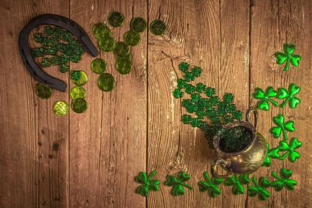 St. Patricks Day composition. Shamrocks, horseshoe, coins and silver pot on vintage style wood background. St.Patrick's day holiday symbol. Top view, copy space.