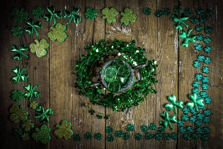 St. Patricks Day composition. Shamrock wreath, shamrocks and silver pot on an old rustic wood background. St.Patrick's day holiday symbol. Top view.