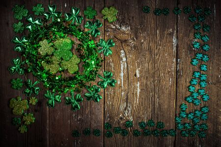 St. Patricks Day composition. Shamrock wreath, shamrocks on an old rustic wood background. St.Patrick's day holiday symbol. Top view, copy space. Stock Photo