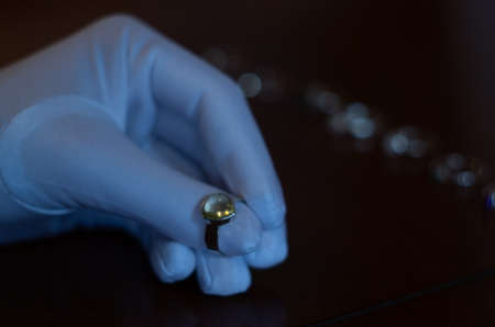 a jeweler examines a piece of jewelry in a white glove Stockfoto
