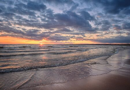 Baltic Sea panorama at sunset with shore waves and sun on the horizon.