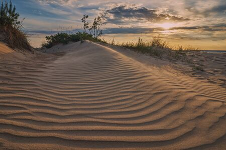 Sandy dune on the Baltic Sea and the summer setting sun. Stock Photo