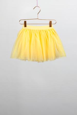 hildren skirt yellow hanger on gray background. Stock Photo