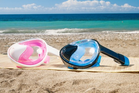 Dive mask and snorkel, snorkelling on sand.