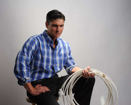the handsome cowboy poses for the photo. Stock Photo