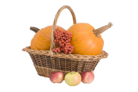 Wattled basket with two pumpkins near to which three apples lie, isolated on white photo