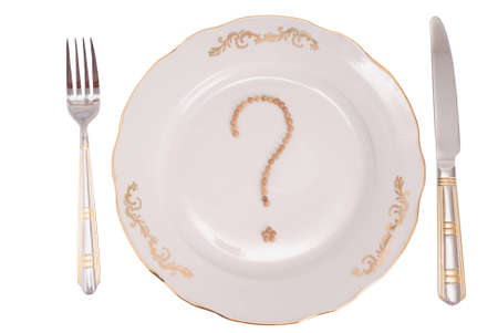 The conceptual image on a theme What to eat?. A set of tablewares on a white background. On a plate the sign on a question from lentil is laid out. photo