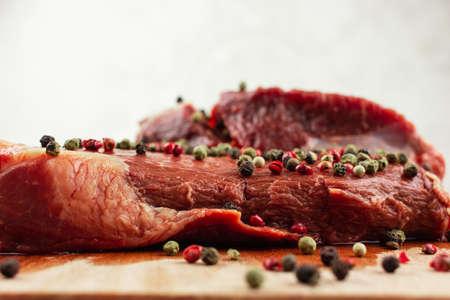 a piece of raw beef seasoned with pepper Banco de Imagens