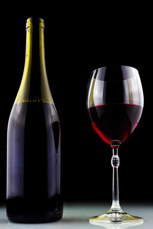 wine bottle and glass on black background