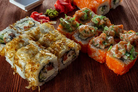 sushi rolls with salmon and smoked eel on a wooden table Imagens