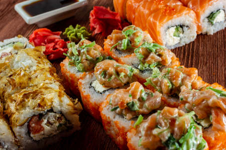 set of sushi rolls with salmon and smoked eel, Philadelphia cheese, served on a wooden table Imagens