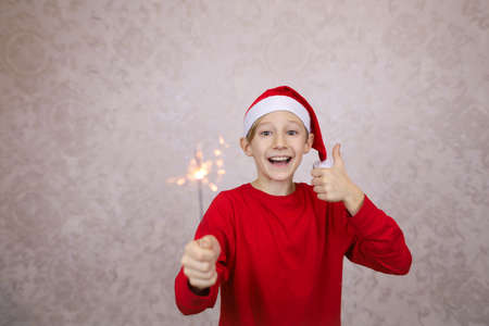 cheerful boy in a red jacket and Santa Claus hat with sparklers on a light background