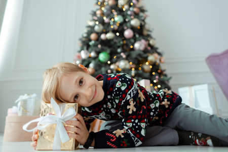 a child in a new year's sweater is lying on a Christmas gift