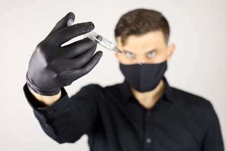 a man wearing black medical gloves and a protective mask holds an injection syringe at arm's length