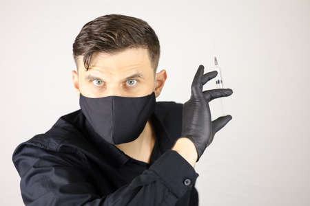 a man wearing medical gloves and a protective mask with a syringe in his hand.