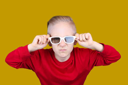 a child in a red jacket holds his hands behind his glasses on a yellow background
