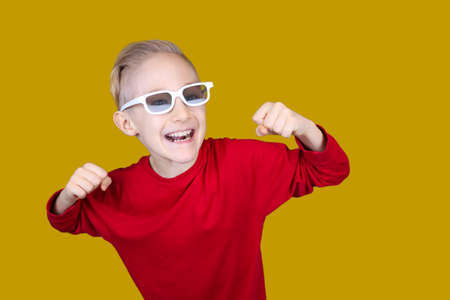 a child in children's 3D glasses joyfully raises his hands Stock fotó