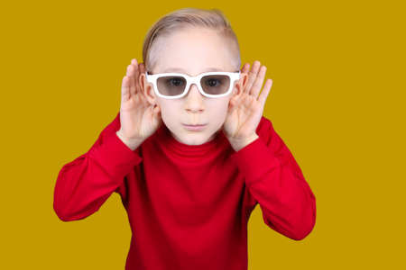 a child in 3D glasses puts his hand to his ear and tries to hear something